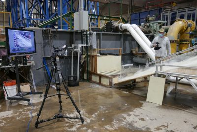 Associate Professor Chris Thornton uses a video camera to give stakeholders a close-up view as water rushes down the spillway model at CSU's Hydraulics Lab. Real-time data from the model is displayed on the screen on the left