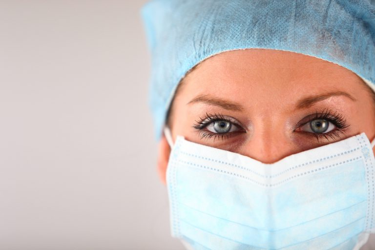 Female with surgical mask and head cap