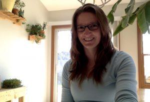 Ingrid Bridge, graduate student advisor in SE, standing in her kitchen with plants behind her.