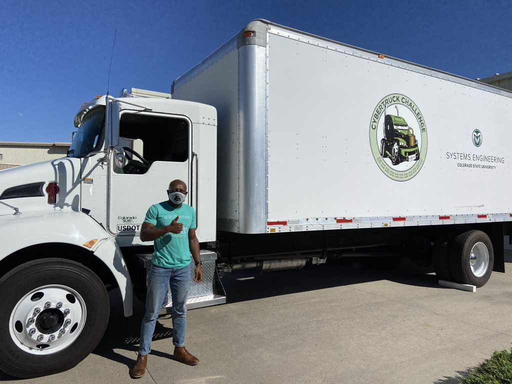 David Nnaji, a second-year master's student in systems engineering, standing next to the Systems Engineering CyberTruck Challenge truck.