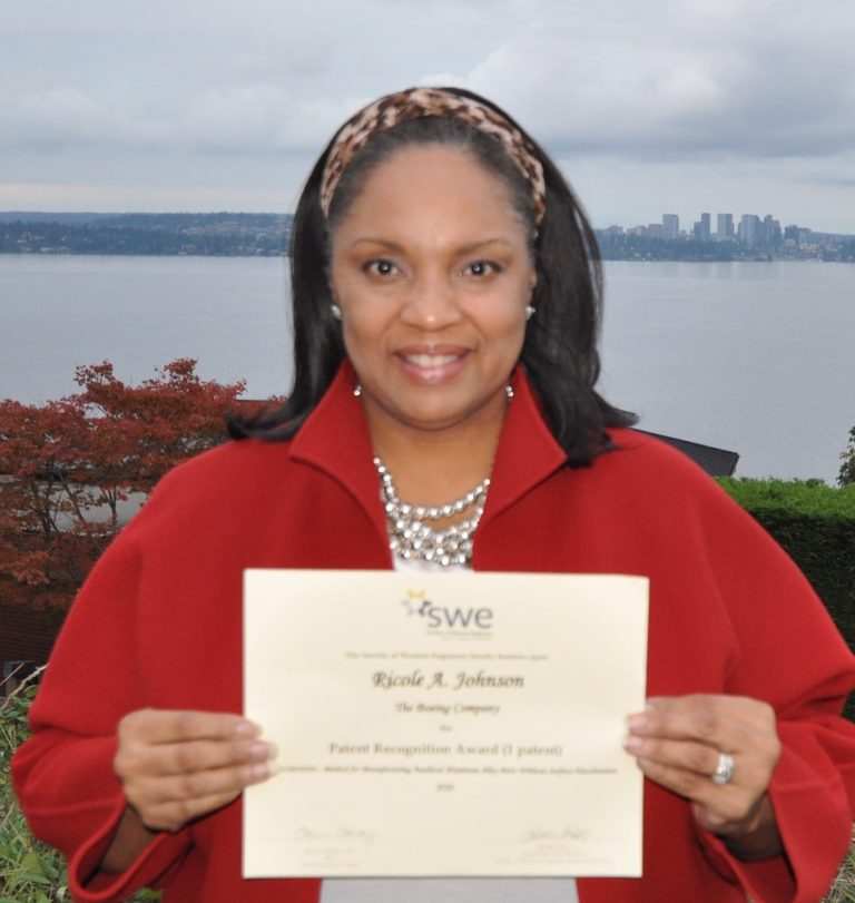 """Ricole Johnson, a Colorado State University systems engineering Ph.D. student, holds her """"Patent Recognition Award"""" from the Society of Women Engineers."""