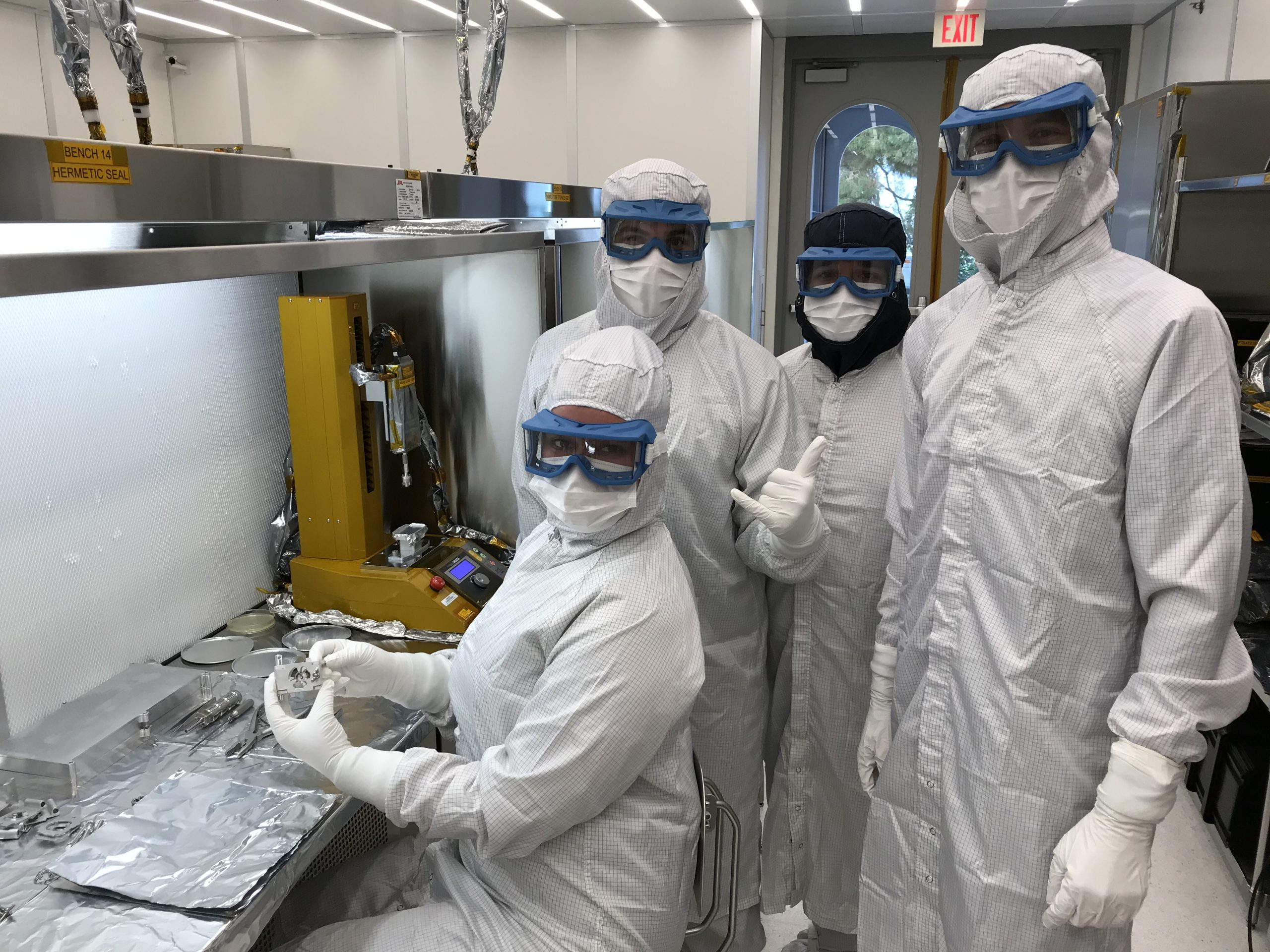 Four NASA scientists dressed in white lab clothes
