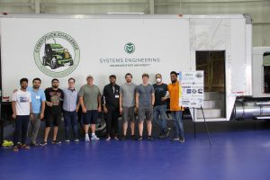 Group of students standing in front of a white truck with a green CSU Systems Engineering logo and CyberTruck challenge logo