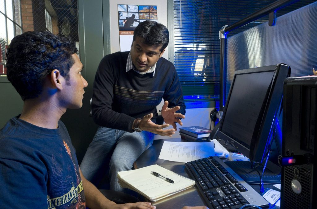 Siddharth Suryanarayanan, Assistant Professor of Electrical and Computer Engineering works with students at the Engines and Energy Conversion Laboratory. October 21, 2011 (Photo Credit: Colorado State University Photography)