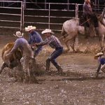 A ranch rodeo team struggles to complete their event due to the muddy conditions of the Baca County Fair rodeo arena.