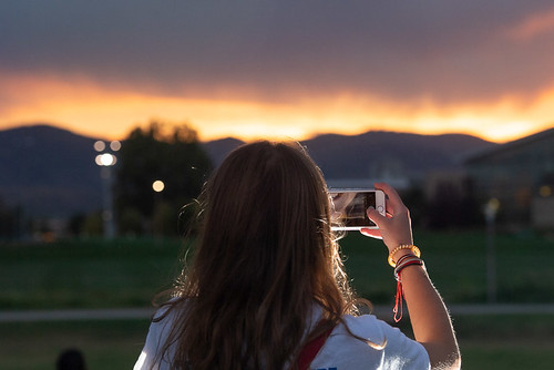 A student snapping a shot of the sun setting over CSU's rec center