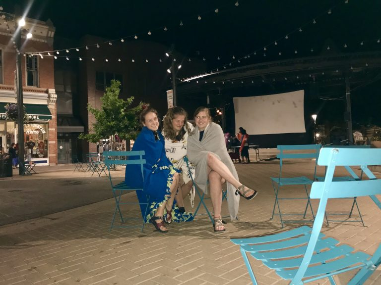 Thee friends in Old Town Square at night.
