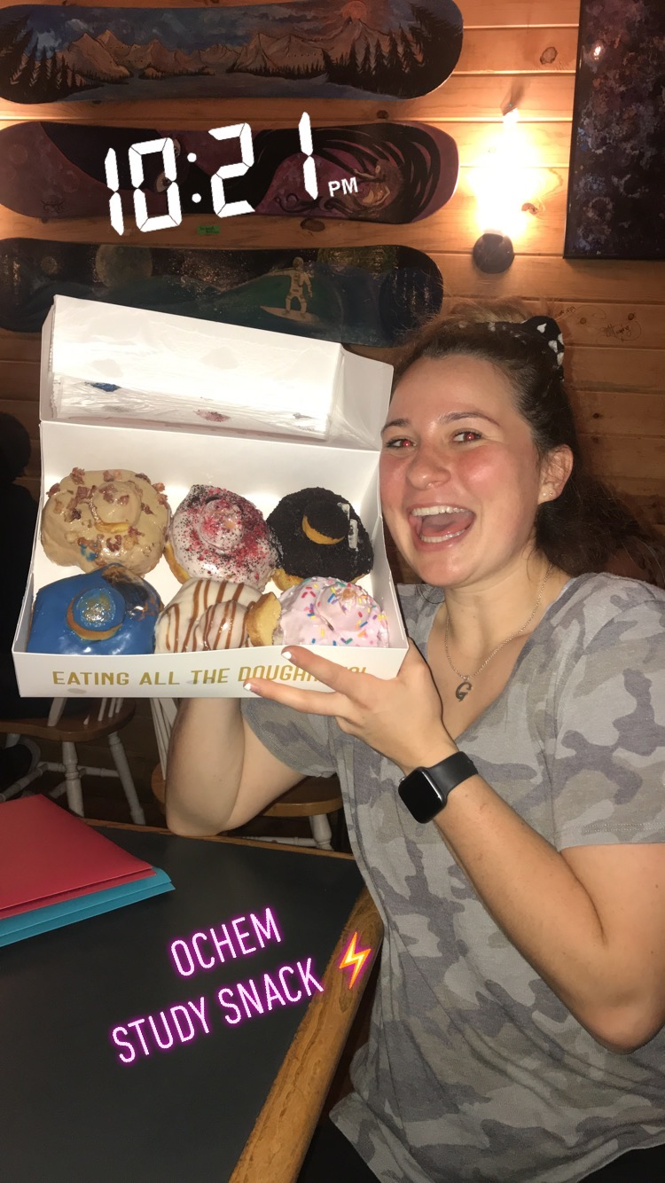Chemistry student holds up a box of donuts