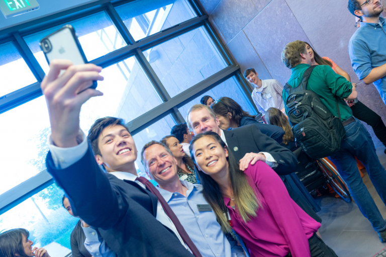 Two students take a selfie with the deans of engineering