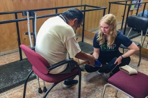 A student fits a prosthetic to a patient