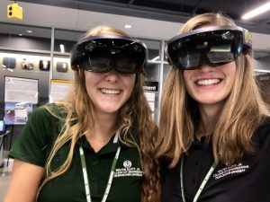 Two students weating augmented reality goggles